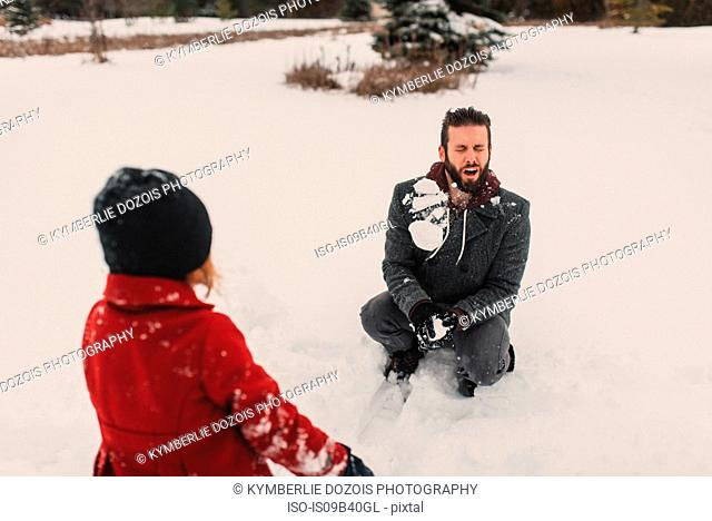 Girl throwing snowball at her father