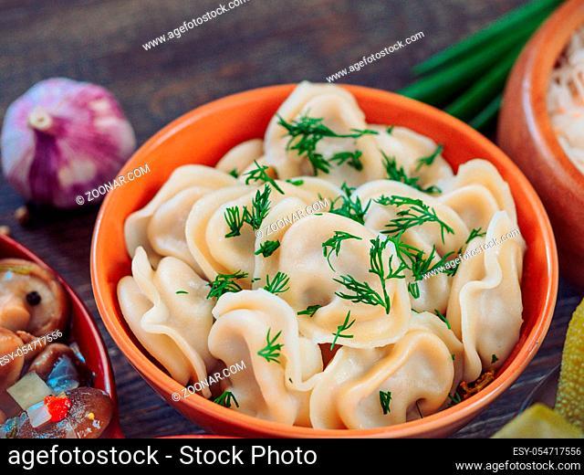 Closeup view of traditional russian food - pelmeni, ravioli or meat dumplings - on brown wooden table. Served with marinated mushrooms, sauerkraut