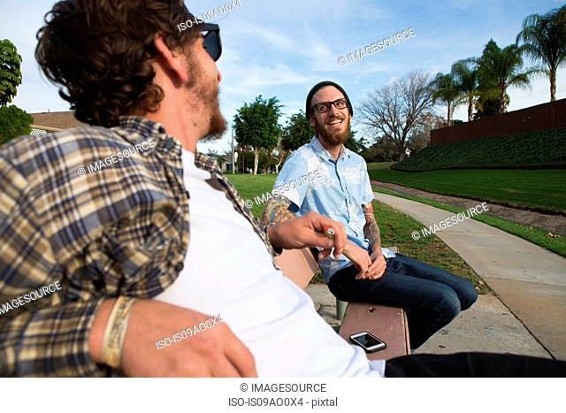Two young male friends chatting on suburban bench