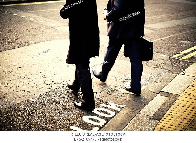 Two unrecognizable executives across a street with a briefcase. London, England, UK