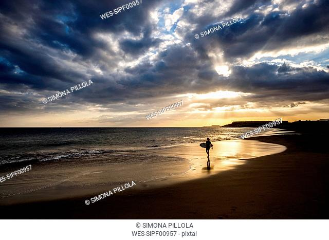 Spain, Tenerife, boy carrying surfboard on the beach at sunset