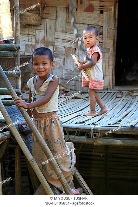An ethnic Marma child climbs on the ladder at his courtyard at Tindu Bandarban, Bangladesh December 2009