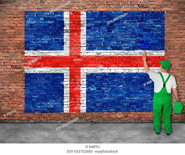 House painter paints flag of Iceland on old brick wall, view from behind