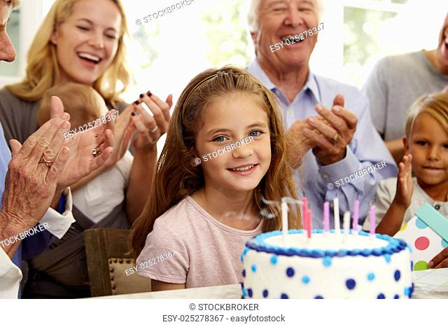 Girl Blows Out Birthday Cake Candles At Family Party