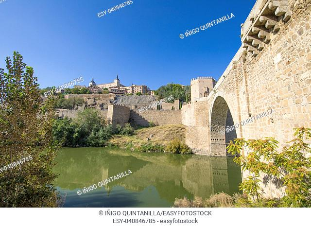 Alcazar from green water river Tagus, Tajo in Spanish, Alcantara arch bridge, landmark and monument from ancient Roman age, in Toledo city, Spain, Europe