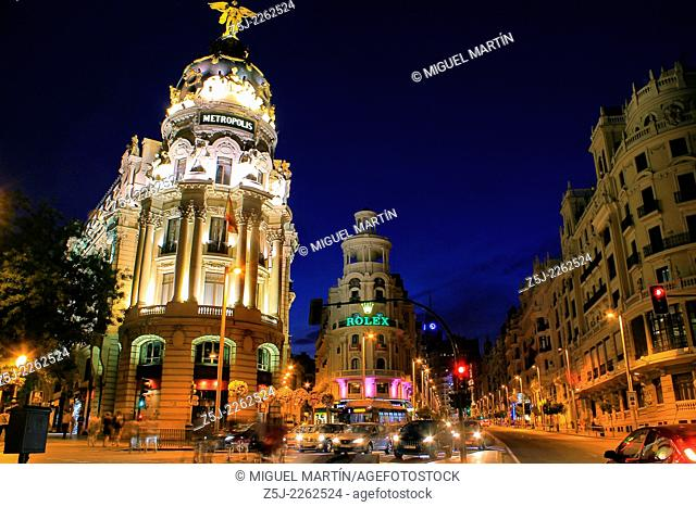 Twilight scene at street junction between Alcalá street and Gran Vía, one of the busiest in Madrid, framed by some notable landmarks like Metrópolis Building...