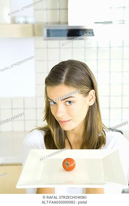 Young woman holding out tray with single tomato