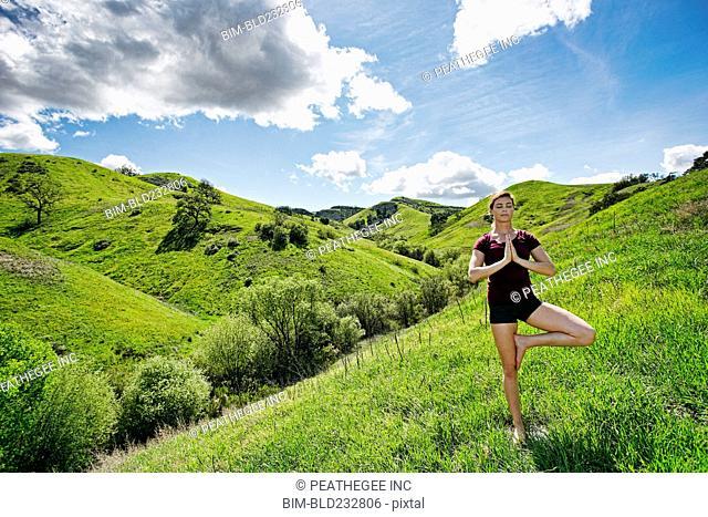 Caucasian woman doing yoga on hill