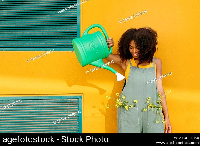 Young woman wearing overalls with watering can and yellow flowers in pockets