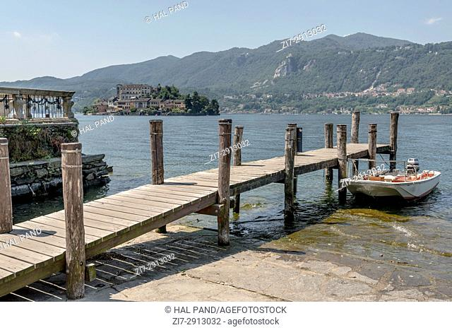 small wooden pier at Orta lake, shot on bright summer day at Orta San Giulio with island in background, Novara, Cusio, Italy