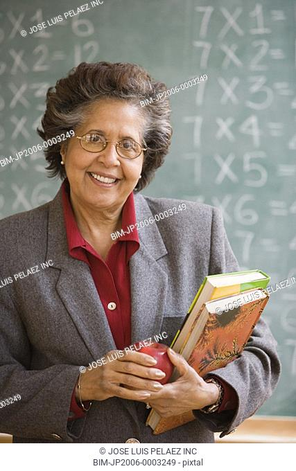 Senior Hispanic female teacher in front of blackboard
