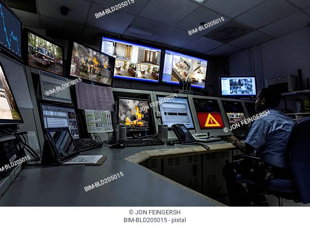 African American security officer working in control room