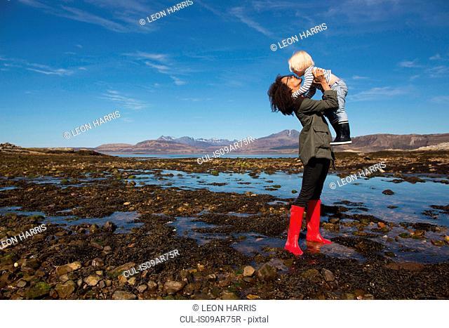 Mother holding son by Loch Eishort, Isle of Skye, Hebrides, Scotland