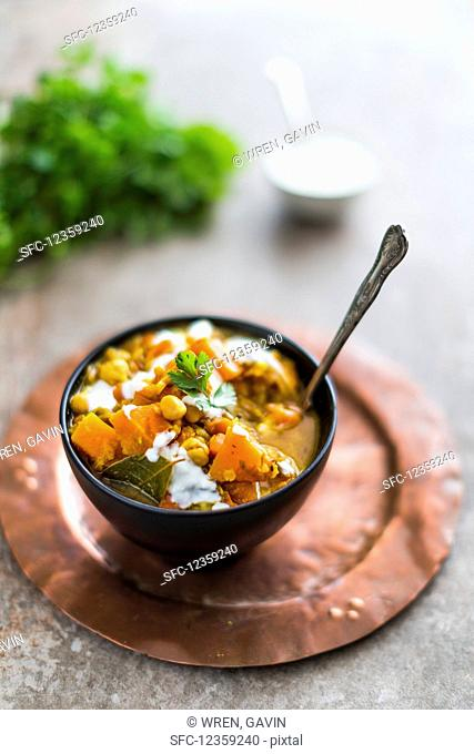 A black bowl on a copper plate filled with chunky butternut squash, lentil and chickpea soup with ginger, garlic, spices and topped with coriander