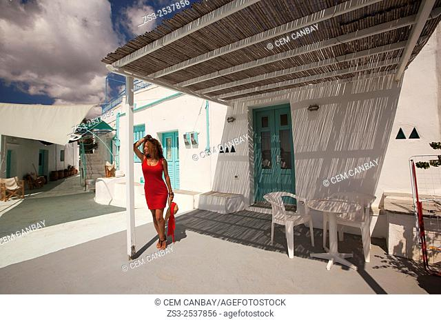 Woman posing at the terrace of a whitewashed Cyclades house in Faros village, Sifnos, Cyclades Islands, Greek Islands, Greece, Europe