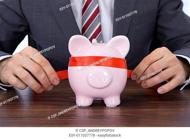 Businessman Covering Piggybank's Eyes With Ribbon