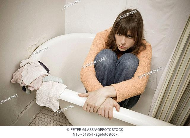 Young woman, wearing her street clothes,  sitting in her bathtub