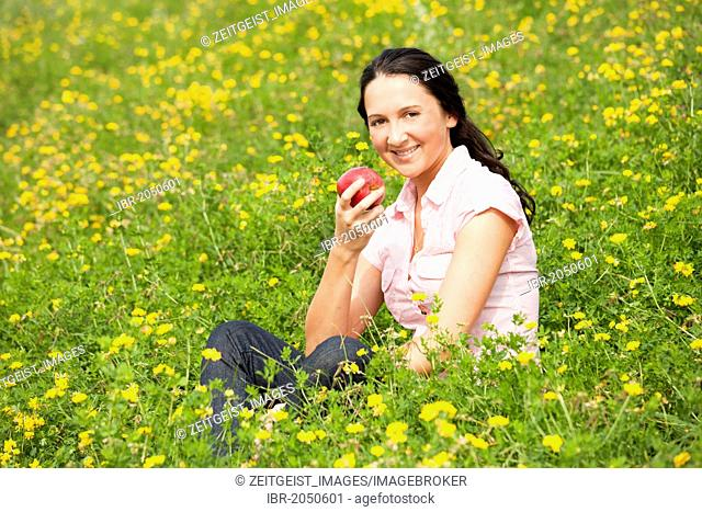 Young woman sitting on a meadow, eating an apple
