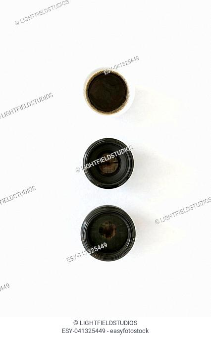 Top view of two photographic lenses and white coffee mug on white tabletop