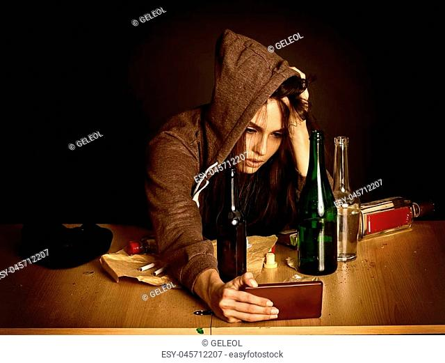 Woman alcoholism is social problem. Heavy parting with a guy. She in hood and hat with green alcohol bottle in bad mood