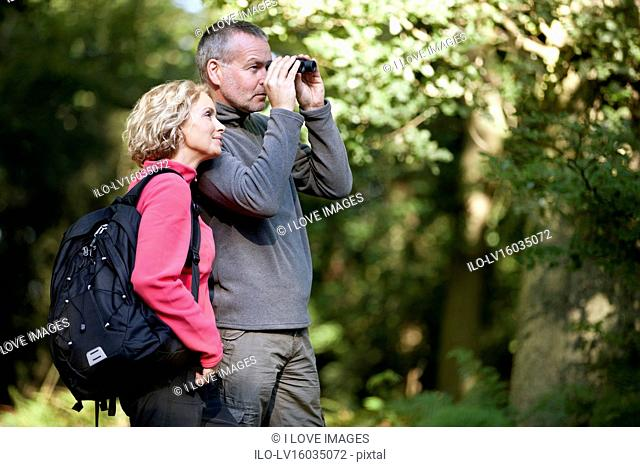 A mature couple standing in the countryside, man looking through binoculars