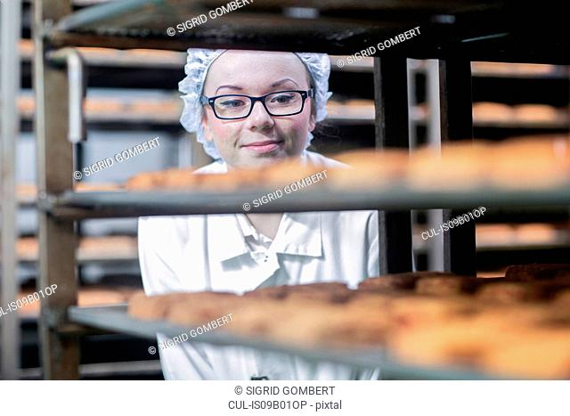 View through shelves of factory worker looking at produce