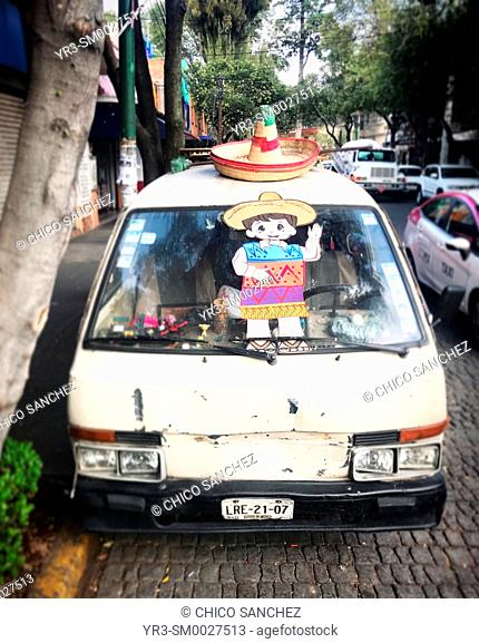 A van decorated with a Mexican sombrero and a sticker of a boy in a street of Mexico City, Mexico