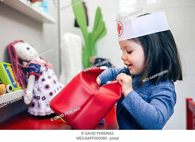 Little girl searching medical toys inside of a red bag