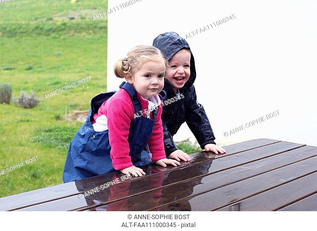 Children climbing on wet picnic table