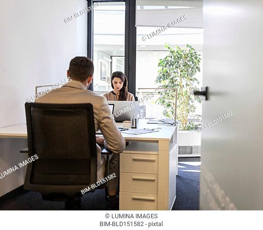 Caucasian business people working at desks in office