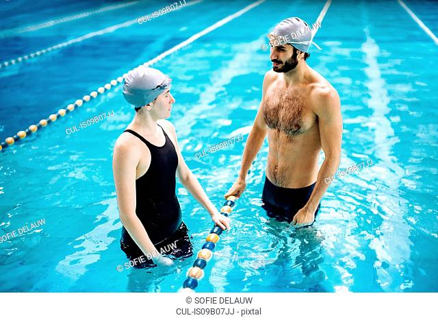 Couple in swimming pool chatting