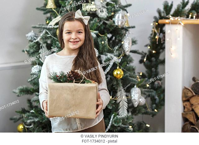 Portrait of smiling girl holding gift against Christmas tree at home