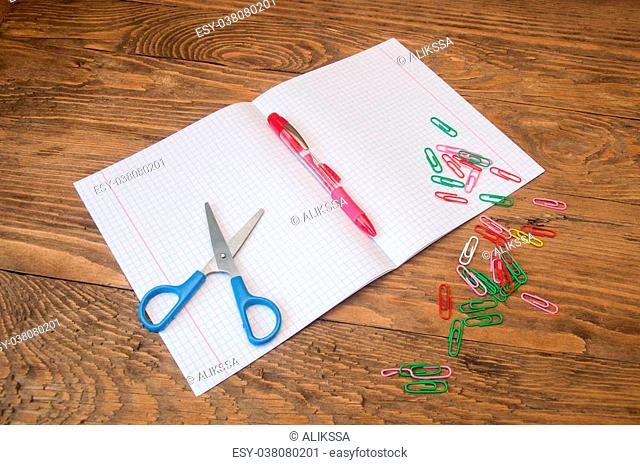 scissors notebook pen and paper clips on a wooden table
