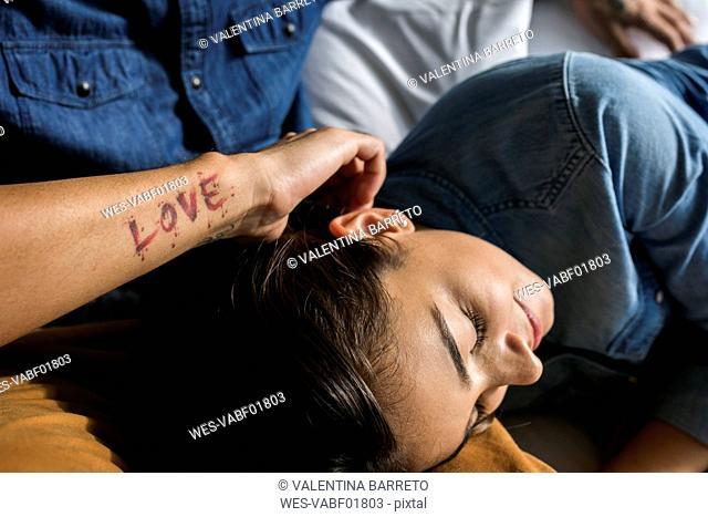 Tattooed man cuddling up with girlfriend