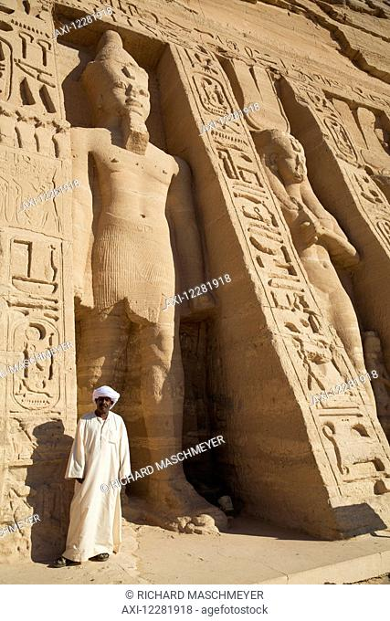 Local man at temple entrance, Ramses II statue (left), Queen Nefetari statue (right), Hathor Temple of Queen Nefertari, Abu Simbel temples; Nubia, Egypt