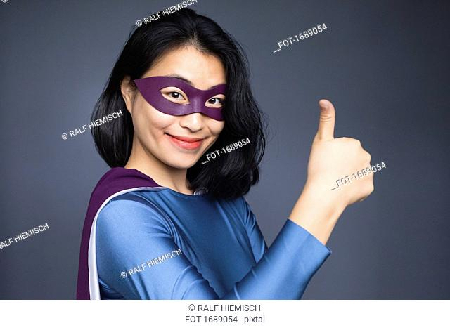 Portrait of confident female superhero gesturing thumbs up against gray background