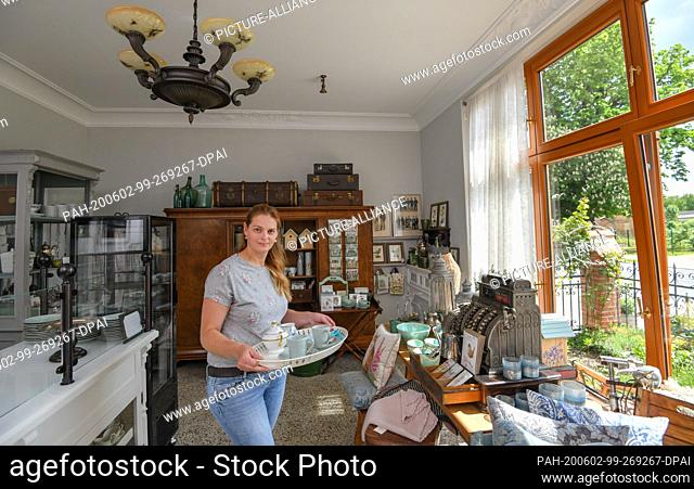 27 May 2020, Brandenburg, Biesenthal: Pamela John, operator of the Imperial Post Office, stands in the sales room with a coffee tray