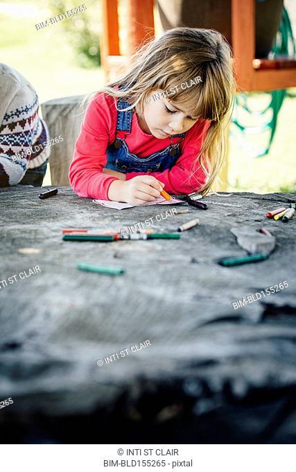 Caucasian girl coloring outdoors
