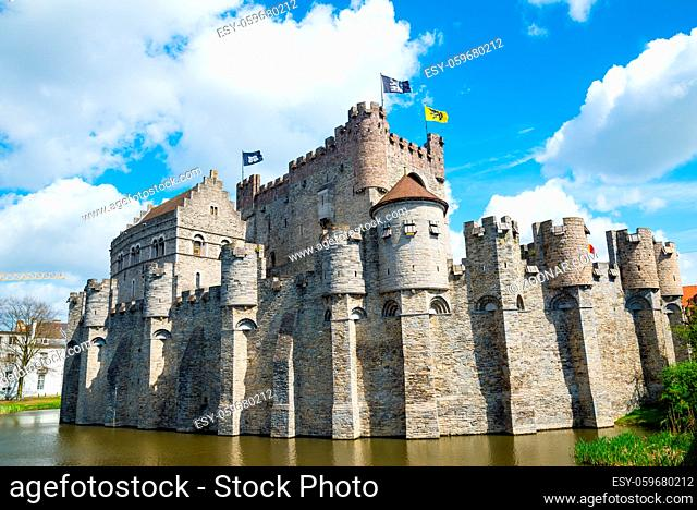 Medieval castle Gravensteen - Castle of the Counts with small windows surrounded by water in moat in Ghent, Flanders, Belgium