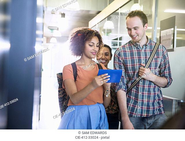 College students using digital tablet walking in corridor