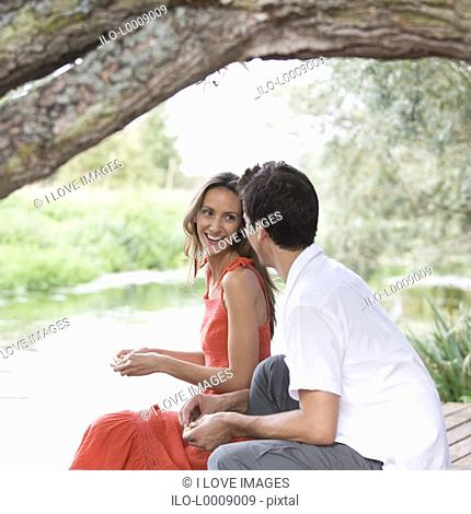 Young couple sitting by a river