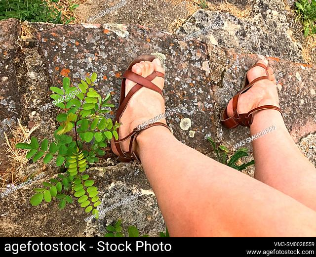 Woman's legs sitting on stone step