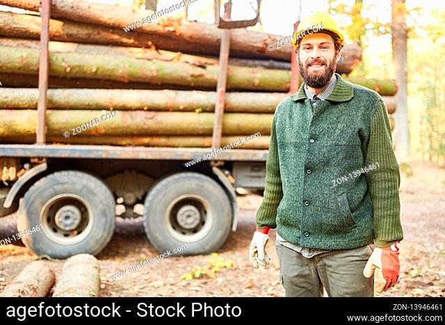Lächelnder Waldarbeiter bei der Holzernte vor einem Langholzwagen im Wald