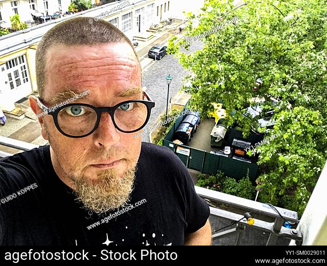Berlin, Germany. Self Porttrait (selfie) of a beglassed man with very short hairdue standing on a third floor balcony with view to a Karl Marx Allee apartment...