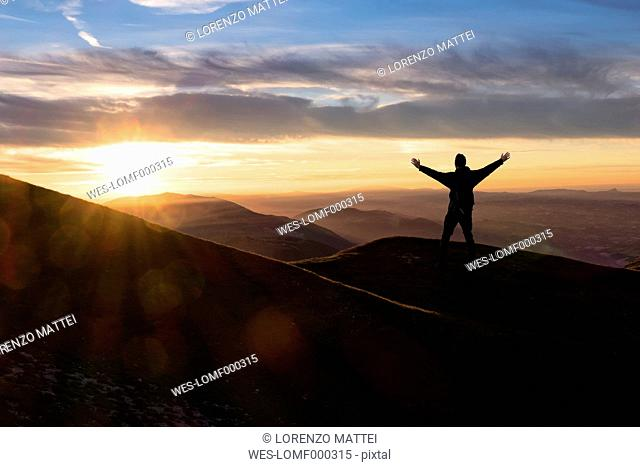 Italy, Umbria, Monte Acuto, Sunset over Umbrian Apennines, hiker with raising arms