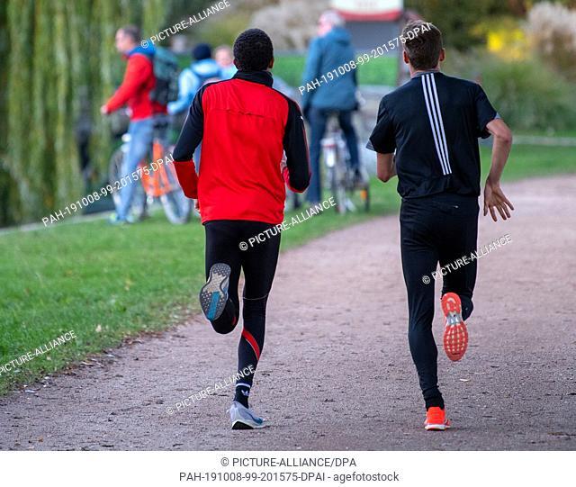 07 October 2019, Brandenburg, Potsdam: Two joggers walk along a path in a green area on the shore of Lake Templin. Photo: Monika Skolimowska/dpa-Zentralbild/dpa