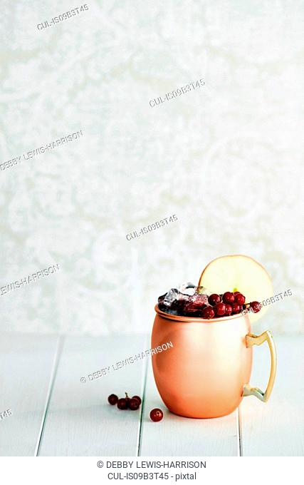 Non-alcoholic cocktail in copper mug with berries and apple slice