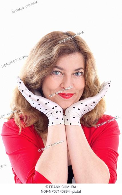 portrait of a middle-aged woman in red with polka-dot gloves - isolated on white