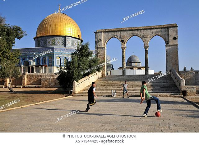 Israel, Jerusalem Old City, Dome of the Rock on Haram esh Sharif Temple Mount a Qanatir The Arch in the foreground  Arab children play soccer