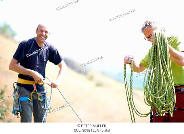 Rock climbers preparing rope looking at camera smiling